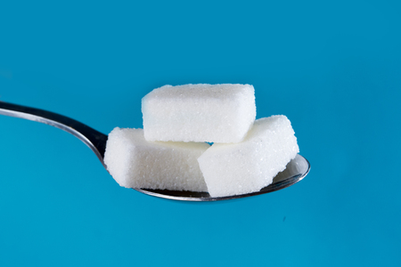 close up tea spoon with a stack of sugar lumps isolated on blue background in sweet and calories abuse and diabetes and unhealthy nutrition concept Stock Photo