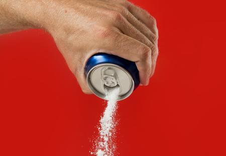 La mano del hombre que sostiene la bebida de refresco puede verter la corriente de azúcar en el contenido dulce y calorías del concepto de bebidas gaseosas y la energía en la nutrición no saludable y el concepto de dieta