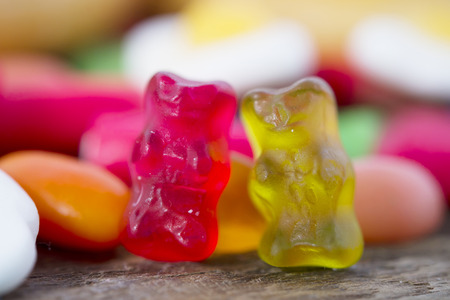 unhealthy but delicious group of sweet sugar bear gummy candies on vintage wooden table in lifestyle nutrition health care and calories abuse and dieting concept