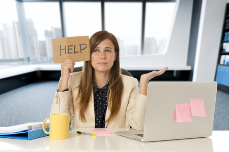 young attractive sad and desperate business woman suffering stress at office laptop computer desk holding help sign looking depressed and overwhelmed in business crisis and problem concept Stock Photo
