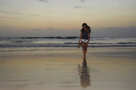 beautiful and attractive african american black woman walking on sunset beach holding sandals relaxed and happy in holiday trip and summer vacation tourism concept Stock Photo