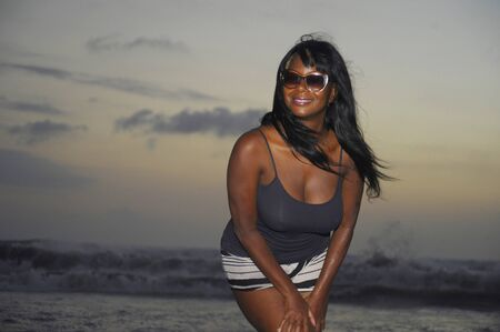 beautiful and attractive african american black woman walking on sunset beach enjoying water and sand relaxed and happy in holiday trip and summer vacation tourism concept