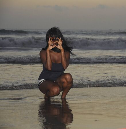 beautiful and attractive african american black woman walking on sunset beach enjoying water and sand doing heart shape with hands relaxed and happy in holiday tourism concept