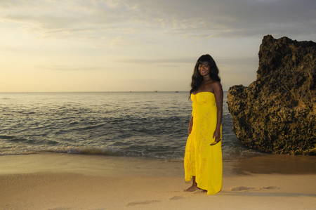 young attractive and glamorous African American black woman in chic and elegant summer dress posing relaxed walking on summer sunset beach in holiday vacation lifestyle concept
