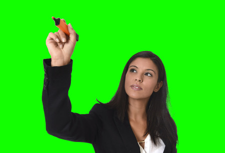 invisible: young attractive latin businesswoman in office suit writing with marker on invisible virtual screen or board isolated on white background in business concept