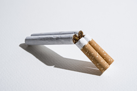 broken cigarette resembling the shape of a loaded weapon gun in anti smoking and health care danger of lung cancer and disease calling to quit the bad habit and tobacco addiction