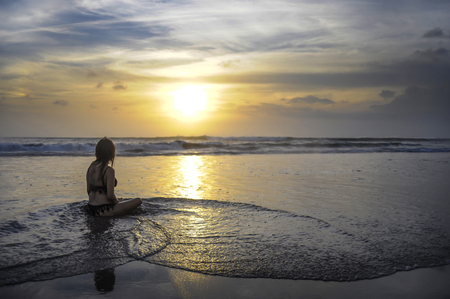 young free woman sitting looking to sea sunset horizon with beautiful sun practicing yoga and meditation at beautiful Asian beach in tourism vacation and summer holiday trip fun Stock Photo