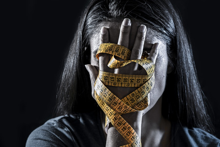 Close up hands wrapped in tailor measure tape covering face of young depressed and worried girl