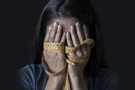 close up hands wrapped in tailor measure tape covering face of young depressed and worried girl suffering anorexia or bulimia nutrition disorder on black background obsessed with diet and overweight