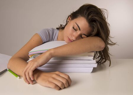 young attractive and beautiful tired student girl leaning on school books pile sleeping tired and exhausted after studying preparing exam looking wasted taking a nap in stress education concept Stock Photo
