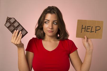 joven y bella mujer adicto dulce sosteniendo pidiendo ayuda resistir la tentación de comer barra de chocolate y romper la dieta en el concepto de estilo de vida saludable de la nutrición y la pérdida de peso