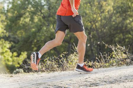 vista lateral del hombre del deporte con las piernas atléticas y musculares rasgadas que corren cuesta abajo del camino en entrenamiento de entrenamiento que activa en el campo en el fondo del otoño en la aptitud y el concepto de estilo de vida saludable Foto de archivo