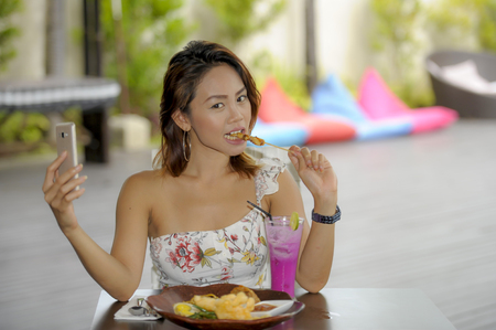 young beautiful and happy Asian girl in sexy dress having brunch or lunch at holiday resort outdoors taking selfie pic with mobile phone camera enjoying relaxed in social media photo concept Stock Photo