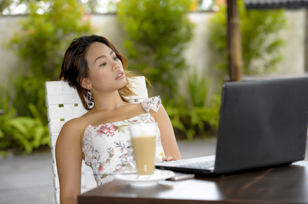 young beautiful and happy Asian woman in chic Summer dress sitting outdoors at nice pool coffee shop having latte breakfast networking or working with laptop computer relaxed and thoughtful