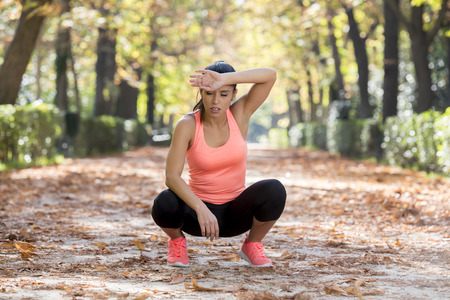 gasping: young beautiful and attractive sport woman in runner sportswear breathing gasping and taking a break tired and exhausted after running workout on Autumn urban city forest park in fitness concept