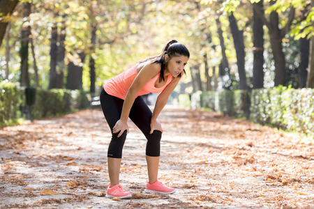 young beautiful and attractive sport woman in runner sportswear breathing gasping and taking a break tired and exhausted after running workout on Autumn urban city forest park in fitness concept