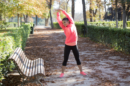 young attractive and beautiful hispanic sport woman in sportswear stretching body next to bench doing flexibility exercises warm up before running workout in Autumn city park background Stock Photo