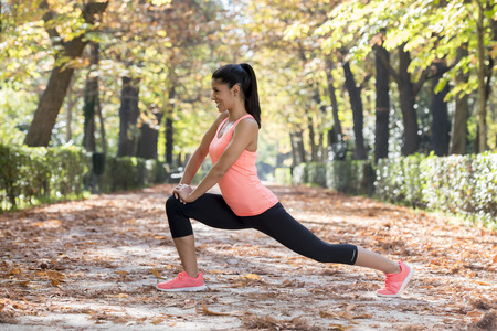 young attractive and beautiful hispanic sport woman in sportswear stretching body next smiling happy doing flexibility exercises warm up before running workout in Autumn city park background