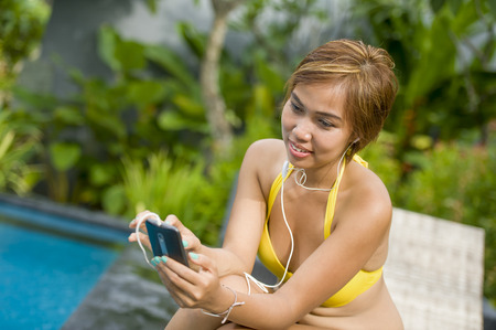 young attractive and happy Asian woman in bikini using social media internet app on mobile phone relaxed at resort swimming pool in communication and holiday vacation relax concept