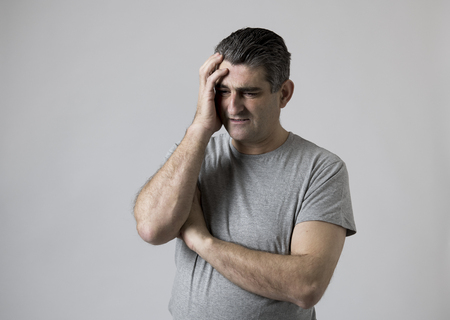portrait of 40s to 50s sad and worried man looking frustrated and hopeless in stress and sorrow face expression isolated on grey background in sadness frustration and life problems concept