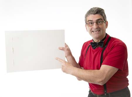 corporate portrait of weird and funny 40s to 50s sales man with bowtie and red shirt pointing blank billboard poster with copy space for adding text and advertising product isolated on white