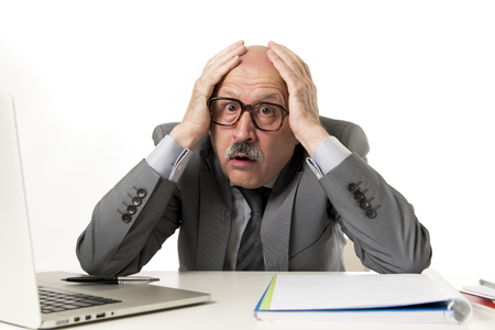 senior mature business man with bald head on his 60s working stressed and frustrated at office computer laptop desk looking desperate and overwhelmed in job mistake and problem concept Imagens