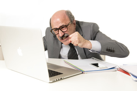 senior mature busy business man with bald head on his 60s working stressed and frustrated at office computer laptop desk looking angry and overwhelmed in job problems and overwork concept