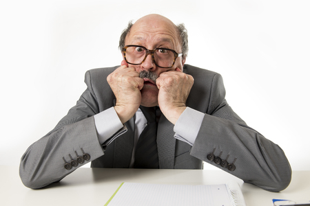 60s bald senior office employee man furious and angry gesturing upset and mad sitting on desk with paperwork in business and job problems and stress concept isolated on white background