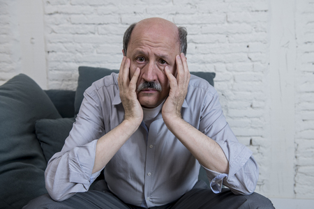 portrait of senior mature old man on his 60s at home couch alone feeling sad and worried suffering pain and depression in sadness face expression in retirement and widower aging frustration concept Stock Photo