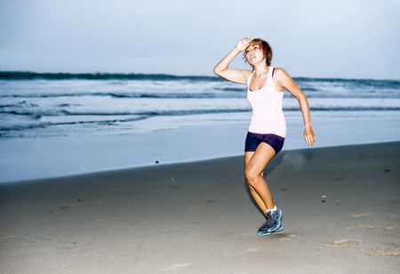 young attractive and fit Asian sport runner woman running on beach sea side looking tired while hard workout in fitness body care and healthy lifestyle concept