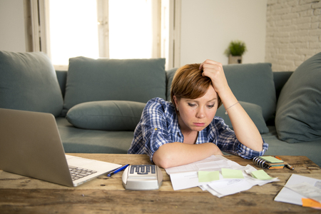 young sad worried and desperate woman banking and accounting home monthly and credit card expenses with computer laptop doing paperwork in living cost stress and paying bills problem Stok Fotoğraf - 91119107