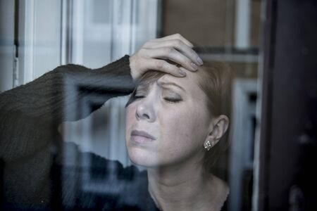 dramatic close up portrait of young beautiful woman thinking and  feeling sad suffering depression at home window looking depressed and worried in lifestyle and life problems concept 스톡 콘텐츠