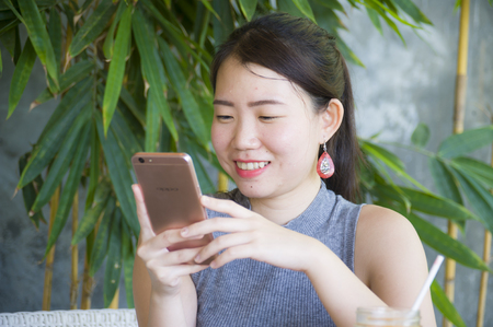 young pretty Chinese Asian woman using internet on mobile phone enjoying relaxed sending text and on line social media chat at coffee shop outdoors