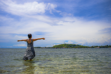 young Asian woman posing with opened arms on beach in Bali Indonesia looking at the blue sea Stock Photo
