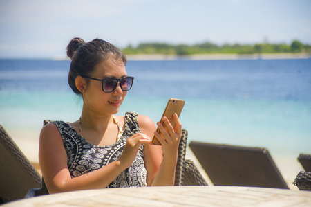 young happy and relaxed Asian Chinese woman using internet social media on mobile phone sending text sitting at island vacation resort on the beach in holidays and communication concept Archivio Fotografico