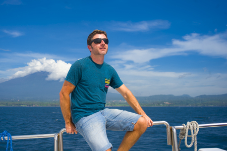 isolated portrait under a Summer blue sky of young attractive and happy Caucasian 30s man having fun enjoying breeze on ship ferry boat deck in holiday vacation travel and happiness concept