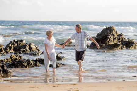 lovely senior mature romantic couple on their 60s or 70s retired walking happy and relaxed on beach sea shore in romantic aging together and retirement husband and wife lifestyle concept Stockfoto - 91839473