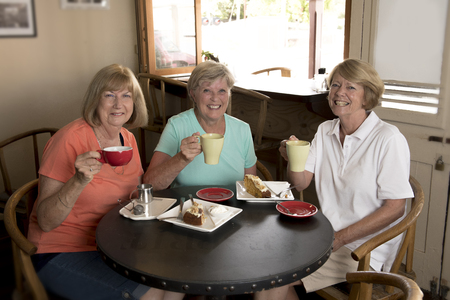 group of three lovely middle age senior mature women girlfriends meeting for coffee and tea with cakes at coffee shop sharing time together enjoying converstion happy and cheerful gossiping