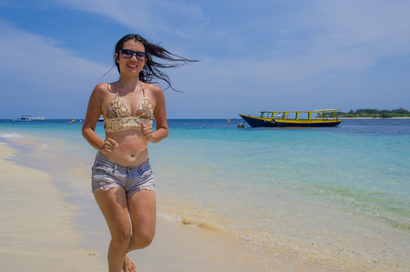young beautiful Chinese Asian girl in shorts and bikini running  on beach sand with amazing beautiful turquoise sea water color enjoying Summer holidays relaxed and happy in travel and tourism concept