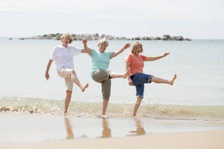 reizende Gruppe von drei älteren reifen Frauen im Ruhestand auf ihren 60ern, die den Spaß genießen zusammen das glückliche Gehen auf das Strandlächeln spielerisch in der weiblichen Freundschaft und in den Freundinnen am Feiertagskonzept haben
