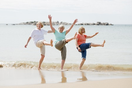 lovely group of three senior mature retired women on their 60s having fun enjoying together happy walking on the beach smiling playful in female friendship and girlfriends on holidays concept Archivio Fotografico