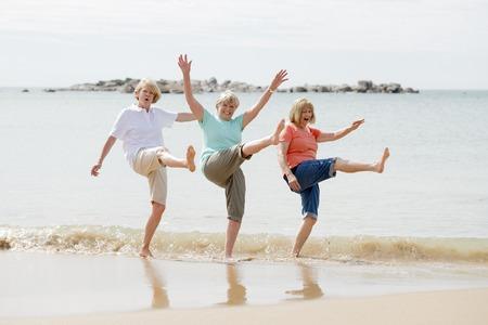Mooie groep van drie senior volwassen gepensioneerde vrouwen op hun jaren '60 plezier samen genieten van gelukkig wandelen op het strand glimlachend speels in vrouwelijke vriendschap en vriendinnen op vakantie concept Stockfoto - 91839651