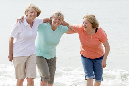 lovely group of three senior mature retired women on their 60s having fun enjoying together happy walking on the beach smiling playful in female friendship and girlfriends on holidays concept Фото со стока
