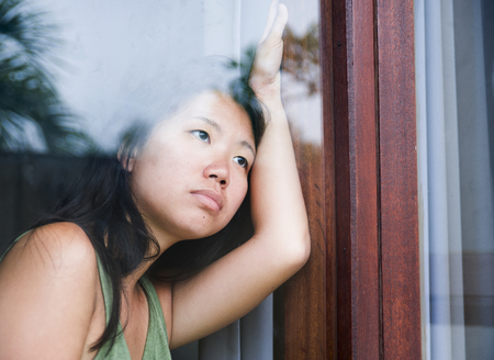 young sad and depressed Asian Chinese woman looking thoughtful through window glass suffering pain and depression in sadness and life problems concept