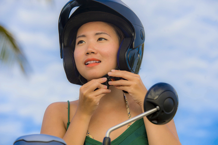Young pretty happy and cute Asian Chinese woman adjusting motorcycle helmet riding on scooter motorbike isolated on a blue sky in safe bike ride safety and security driving concept