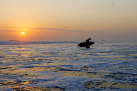 Silhouette of unknown anonymous surfer man holding surf board after surfing on sunset with amazing beautiful sunlight with orange sky and silver sea water in Summer sport and holiday vacation concept Stockfoto