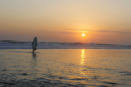Silhouette of unknown anonymous surfer man holding surf board after surfing on sunset with amazing beautiful sunlight with orange sky and silver sea water in Summer sport and holiday vacation concept 版權商用圖片