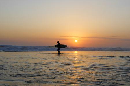 Silhouette de surfeur anonyme inconnu homme tenant une planche de surf après avoir surfé sur le coucher du soleil avec une incroyable belle lumière du soleil avec un ciel orange et de l'eau de mer argentée dans le concept de vacances d'été