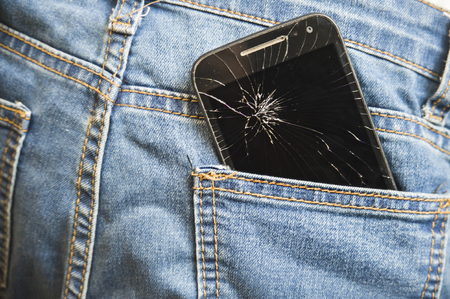 MObile phone broken and cracked touch screen in the back pocket of jeans denim trousers in accident and careless concept Stock Photo