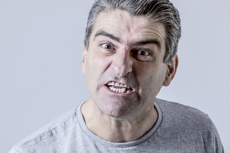 portrait of 40s to 50s white angry and upset guy and crazy furious and aggressive face expression nagging and complaining isolated on grey background in emotions and feelings concept Stock Photo